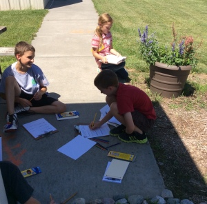 Kids nature journaling in the pollinator habitat.